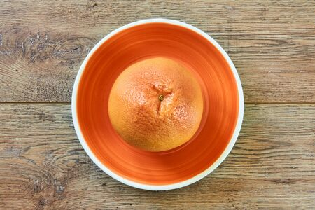 color still life - rosy yellow grapefruit on an orange plate on a cane tablecloth