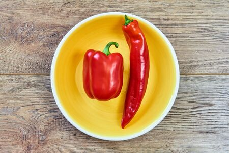 color still life - thin and thick pods of different varieties of sweet pepper on a yellow plate on a wooden tabletop Archivio Fotografico