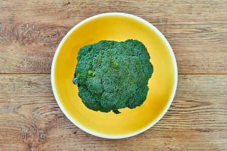 color still life - green broccoli inflorescence on a yellow plate on a wooden tabletop