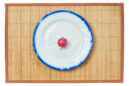 lonely small pink radish on a white plate with a blue rim on a cane serving mat Archivio Fotografico