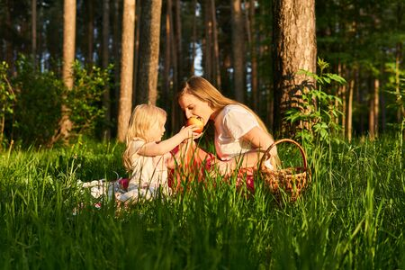little daughter shares apple with her mom during a picnic in the park