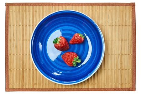 three red strawberries on a blue plate on a cane serving mat