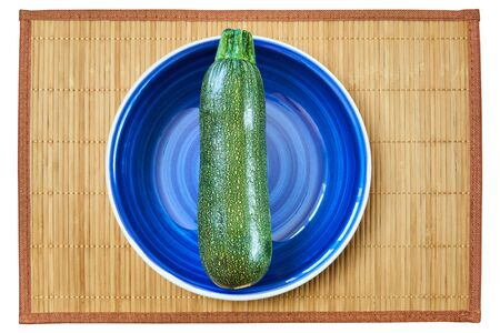 color still life - patterned green zucchini squash on a blue plate on a cane serving mat