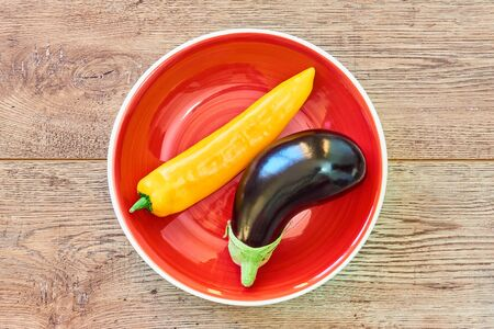 thin yellow pod of sweet pepper and almost black eggplant on a red plate on a wooden tabletop Archivio Fotografico