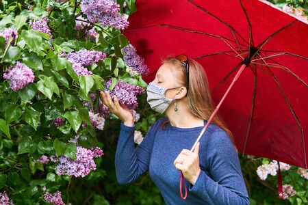 woman in a homemade protective mask tries to smell the lilac inflorescence in the rain outdoors