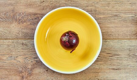 color still life - purple bulb of red sweet onion on a yellow plate on a wooden tabletop Archivio Fotografico