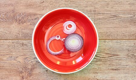 color still life - bulb of sweet purple onion sliced in rings on a red plate on a wooden tabletop Archivio Fotografico