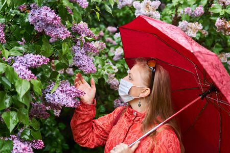 woman in a surgical protective mask tries to smell the lilac inflorescence in the rain outdoors