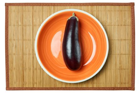 color still life - purple eggplant on a orange plate on a cane place mat Archivio Fotografico