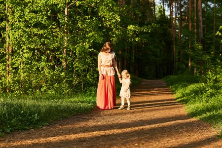 mother and toddler daughter walk along the path in the evening park, hold hands