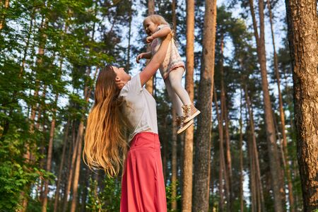 woman plays with her daughter in the park, raising her high up in her arms