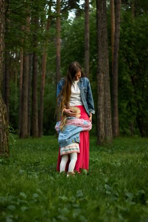 happy baby girl hugs her mom standing on the grass in the park Archivio Fotografico