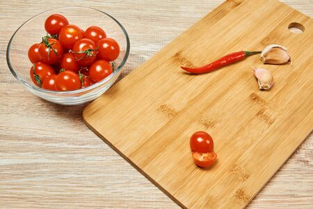 kitchen still life with cherry tomatoes, chili pepper and slices of garlic on a cutting board