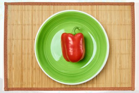 color still life - red pod of sweet bell pepper on a green plate on a cane serving mat