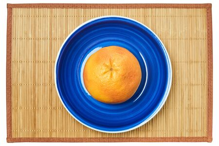 color still life - rosy yellow grapefruit on a blue plate on a cane serving mat Archivio Fotografico
