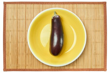 violet ripe eggplant on a yellow plate on a cane serving mat