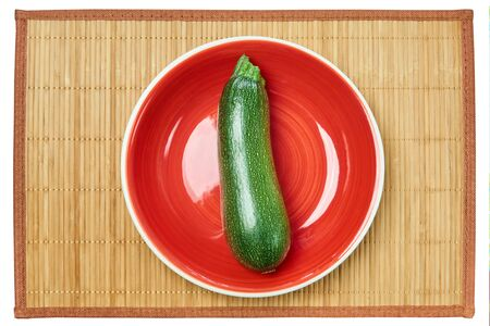 color contrasting still life - patterned green zucchini squash on a red plate on a cane serving mat