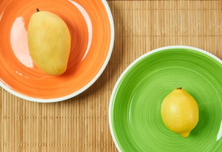 yellow fruits - sweet mango on an orange plate and sour lemon on a green plate - on a cane serving mat