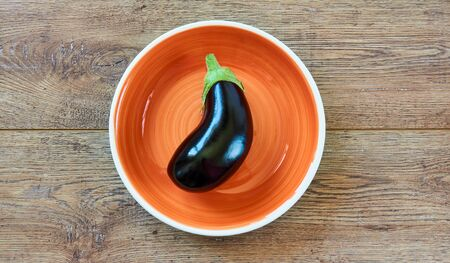 ripe purple, almost black eggplant on a orange plate on a wooden tabletop