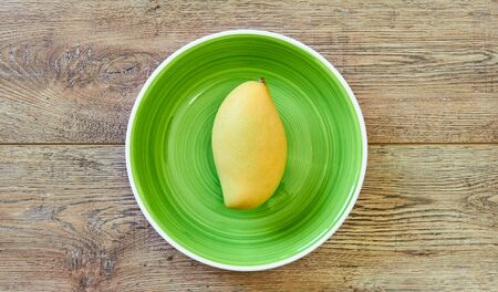 color still life - pale yellow mango fruit on a green plate on a wooden tabletop