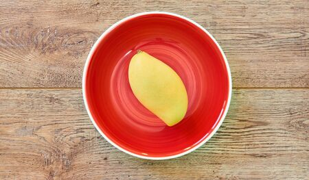 color still life - pale yellow mango fruit on a red plate on a wooden tabletop
