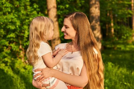 smiling beautiful young woman affectionately looks at her little daughter, who is holding in her arms, on a natural background Archivio Fotografico