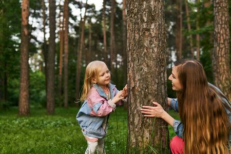 cheerful woman playing with her toddler daughter in the park, hiding behind a tree Archivio Fotografico