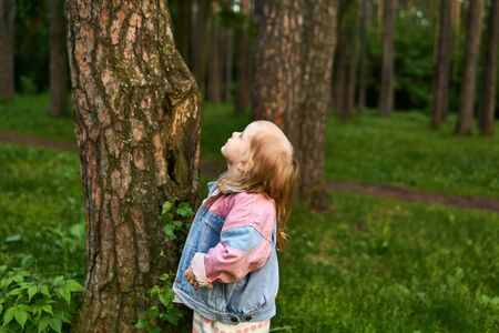 little girl standing next to a tree looks at his crown on a blurred natural background
