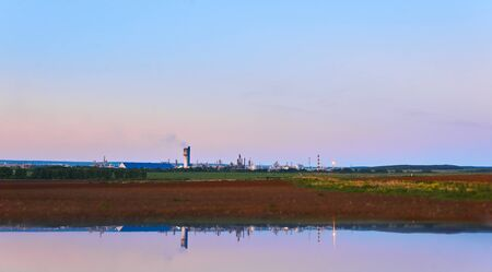 rural landscape with a chemical plant on the horizon reflected in the water; foreground blurred