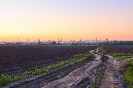 evening rural landscape with plowed fields, dirt road and a huge oil refinery on the horizon