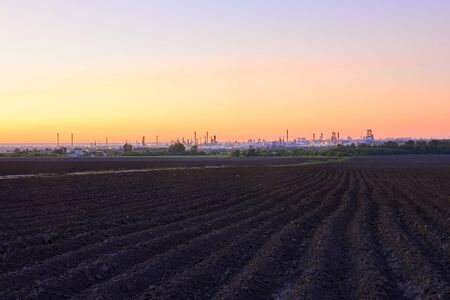 evening rural landscape with plowed fields and a huge oil refinery on the horizon
