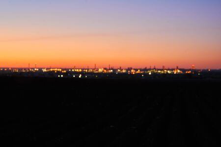 specially blurred background - a distant evening city on dark land against the background of the dawn