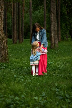 happy laughing baby girl hugs her mom standing on the grass in the park