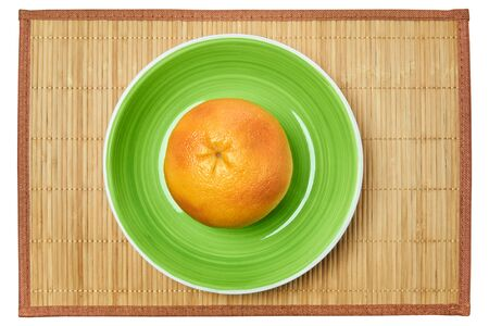 color still life - ripe yellow grapefruit on a green plate on a cane place mat