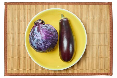 small purple head of red cabbage and purple brown eggplant on a yellow plate on a cane place mat