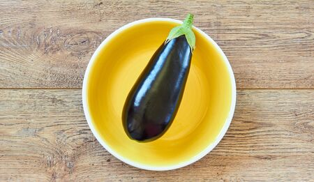 color still life - dark blue eggplant on a yellow plate on a wooden tabletop