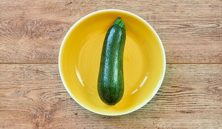 color still life - pale green zucchini squash with patterned skin on a yellow plate on a wooden tabletop
