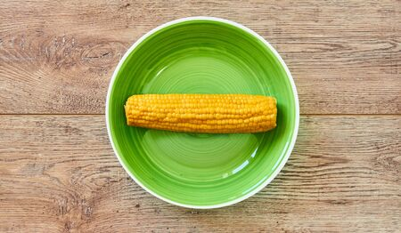 contrast still life - yellow cob of boiled corn on a green plate on a wooden tabletop Archivio Fotografico