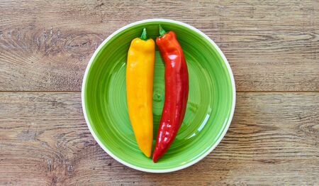 color still life - yellow and red pods of pepper on a green plate on a red plate on a wooden tabletop