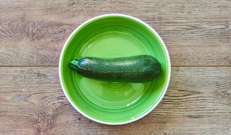 color still life - pale green zucchini squash with patterned skin on a green plate on a wooden tabletop