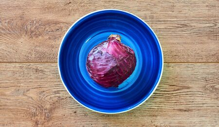 color still life - purple head of red cabbage on a deep blue plate on a wooden tabletop Archivio Fotografico