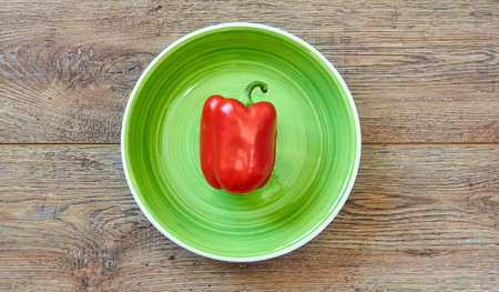 color still life - red bell pepper on a green plate on a wooden tabletop Banco de Imagens