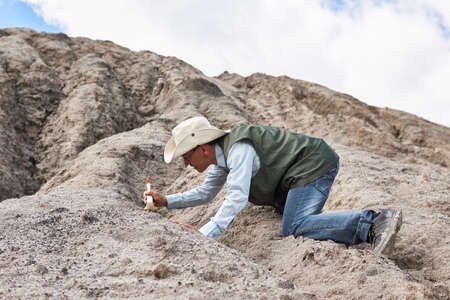 man archaeologist or paleontologist cleans the find with a brush in the desert