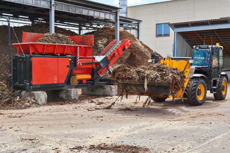 bucket loader loads wood bark into an industrial tree chipper in a woodworking industry