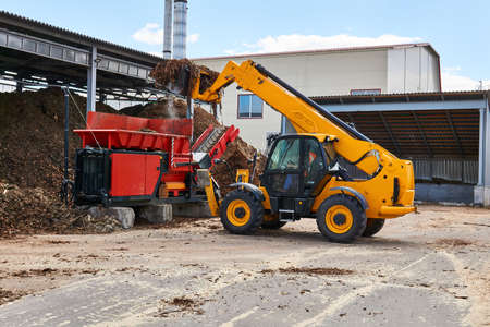 bucket loader loads wood bark into an industrial woodchipper in a woodworking industry