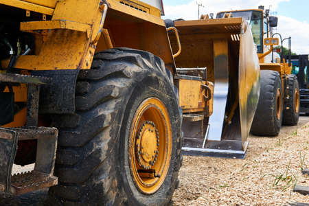 row of standing heavy construction wheeled bulldozers close up