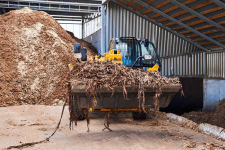 bucket loader moving wood bark in a woodworking industry Banco de Imagens
