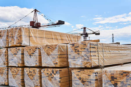 packaged freshly made boards and cranes in the background in the yard of the woodworking production