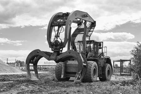 indusrtial dual function grapple skidder stands on the ground outdoors