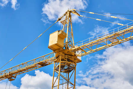 fragment of a yellow construction tower crane against a blue sky with clouds